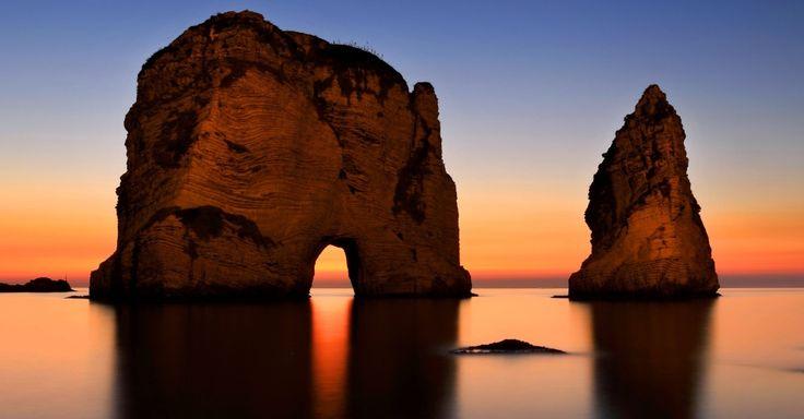 """Conhecidas, entre outros nomes, como """"Rochas da Raouché"""", estas duas formações rochosas marcam uma parte do mar Mediterrâneo que banha a cidade de Beirute, no Líbano. Destruída por uma sangrenta guerra civil entre os anos 70 e 90 (e posteriormente bombardeada por Israel), a capital libanesa ainda vive sob as tensões do Oriente Médio, mas abriga lindas paisagens (como a vista nesta foto) e uma vida noturna vibrante. Durante o dia, casais passeiam tranquilamente pelo seu belo calçadão à…"""