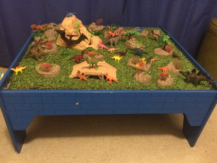 """My Kmart hack: My sons Kmart train table converted into """"Dinosaur Land"""". Fake grass square from bunnings and dinosaur pack from #kmart"""