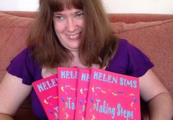 Helen Sims, seated, holding her books.    #TakingSteps #Disability #Books #Activism #MentalHealth #Poetry #Writing #HelenSims #Shortstories