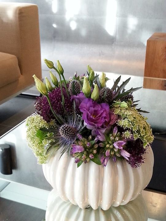 Purple and white flowers in a cream vase
