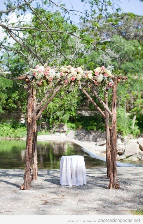Altar hecho con troncos y ramas y flores, ideal para una boda en patio o jardín