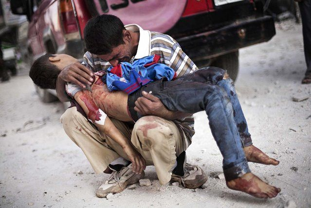 Aman cries while holding the body of his son, one of at least 34 people killed in the bombings, near Dar El Shifa hospital in Aleppo, Syria, on October 3, 2012. (Photo by Manu Brabo/Associated Press)