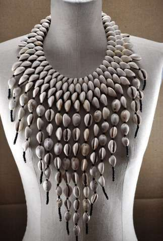 """Necklace   Baba Berthe. Baltimore, Maryland,   United States ~Cowrie shells and glass beads.  """"Artist Baba Berthe's seashell necklaces are stunning displays of natural nautical beach beauty. The complex cowrie collars are crafted out of hundreds of small shells collected by the artist. They are then intricately strung together into a cascading collar of beachy beads."""""""