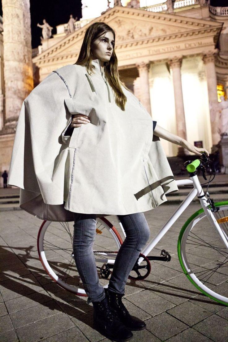 Woman modeling a white cape on a white bike.