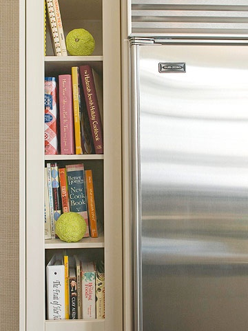 Serving as bookends for the twin refrigerator-freezer units, these slender high-rise, built-in shelves store cookbooks and display collectables. Besides giving the cook quick access to recipes, the shelves camouflage the true depth of the appliances.