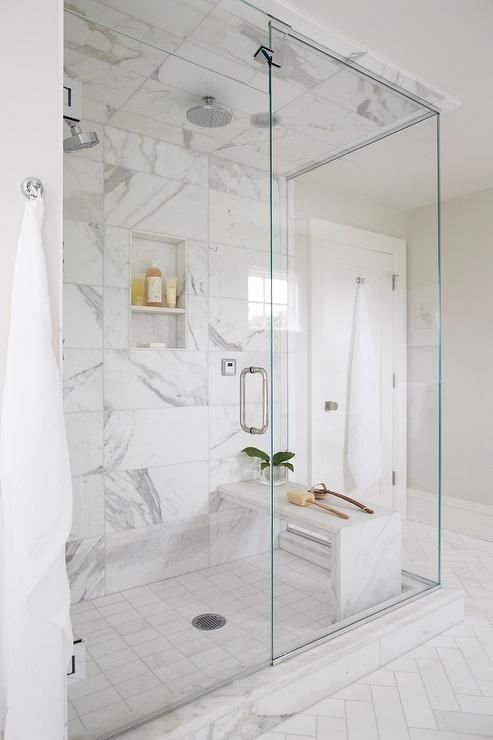 Beautifully appointed seamless glass shower is fitted with marble grid floor tiles placed beneath a marble waterfall bench fixed against large marble subway wall tiles framing a tiled niche.