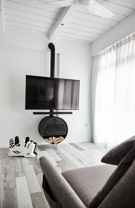A fireplace-inspired TV console with a recycled oil barrel in the living room. Besides aesthetics, it also serves to hide electronic devices and wiring.