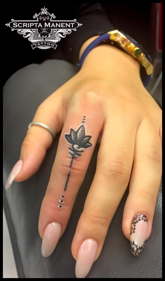 Lotus in finger tattoo