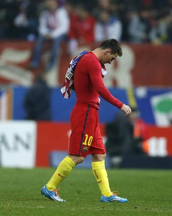 Barcelona's Lionel Messi from Argentina leaves the field holding Atletico's Arda Turan's shirt at the end of a Spanish La Liga s...