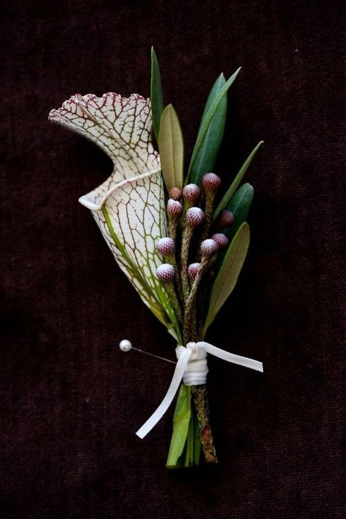This enchanted woodsy wedding has this gorgeous boutonniere for the groom in a lovely dark green color