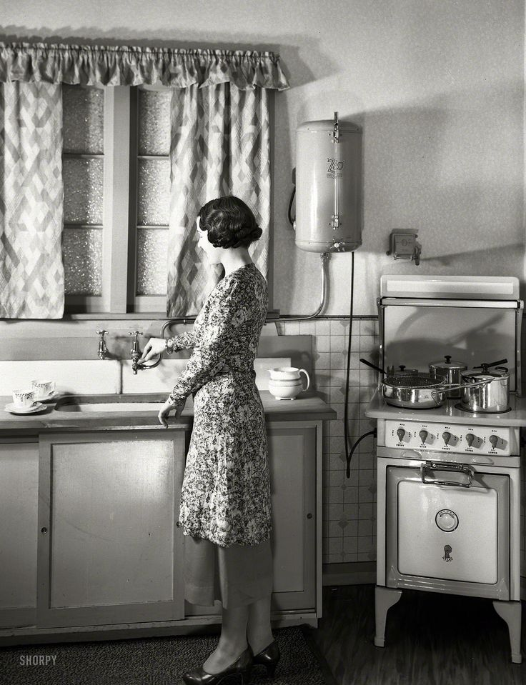 """New Zealand circa 1930s. """"Model at sink in kitchen equipped with Atlas electric stove and Zip water heater."""" Studio of Gordon Burt, Wellington"""