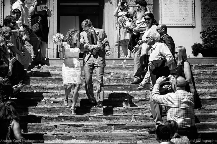 Romantic civil wedding in Cortona, Italy - the couple walks down the Town Hall staircase greeted by family & friends who throw confetti. Wedding planning by www.tuscantoursandweddings.com
