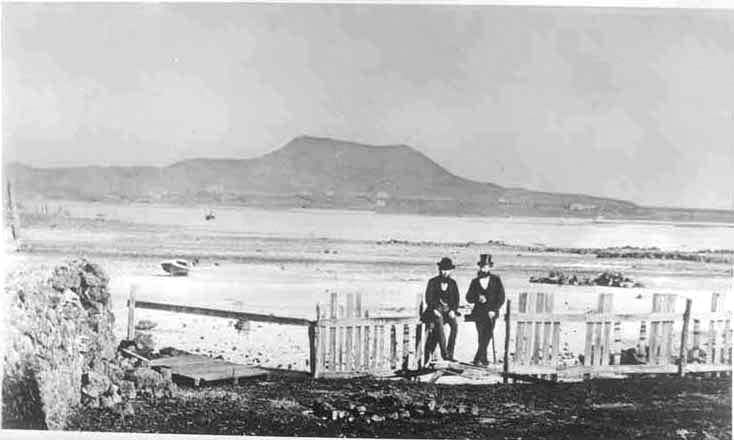 c1875. Looking south from the vicinity of the foot of Hill Street, Onehunga across the Manukau Harbour towards Mangere Mountain showing Matthew Sims and Captain Parnall conversing by the fence (foreground) and Saint James Church (left of centre in the distance). Sir George Grey Special Collections, Auckland Libraries, 7-A3412.
