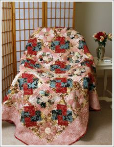 Kiku Blossm quilt is a mix of traditional patchwork and applique. The eight-sided chrysanthemum block uses English Paper Piecing and applique techniques. The traditional Card Trick block is pieced.