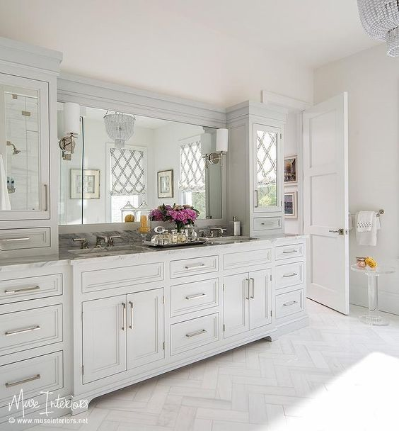 Stunning bathroom features light gray bath vanity cabinets fitted with long polished nickel pulls and mirrored doors topped with gray marble fitted with his and hers sinks alongside a white honed marble herringbone tiled floor.