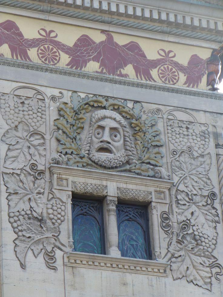Den komiske maske omkranset af egeløv. Vinrankerne rundt om refererer til Dionysos.