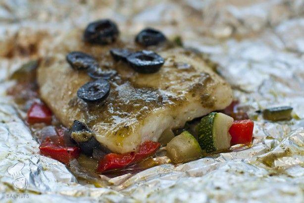 Mediterrane vispakketjes van de bbq. Witvis verpakt in folie met groenten, olijven en pesto en dan op de barbecue. Erg lekker en weer eens wat anders dan de welbekende saté! Lees het recept via de bron!