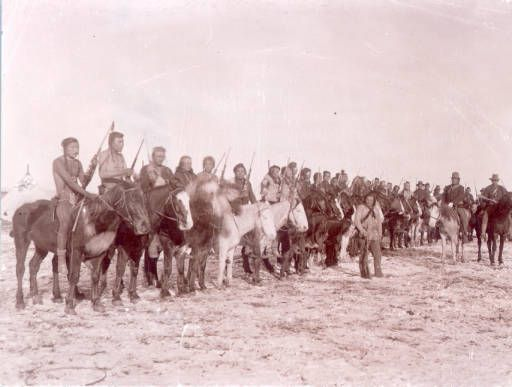 Native American (possibly Crow or Dakota) men on horseback hold rifles and pose in a row probably near Fort Keogh (Custer County), Montana. Some of the men wear braids, buckskin or woven shirts, moccasins and sit bareback on horses. Indian military scouts on horseback, probably under the command of First Lieutenant Edward Casey, wear uniforms, hats and scarves. One man stands and poses with a rifle nearby.