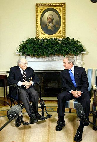 Frank Buckles in a wheel chair is talking to George W. Bush. In the background, above their heads are a plant decoration and a portrait of George Washington.