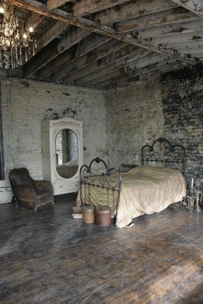 cast iron bed.  club chair. exposed weathered beams.  worn wooden floors.  mismatching brick walls.  this bedroom is everything.