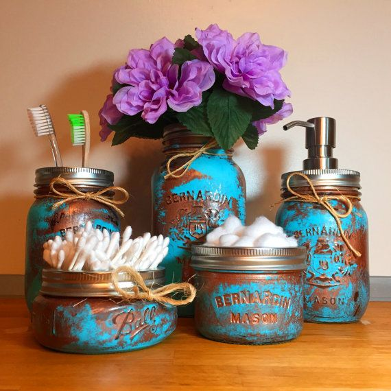 """This copper patina mason jar bathroom gift set, complete with stainless steel soap pump and flower holder/vase, adds the perfect rustic charm to your bathroom. Our unique colours add a gorgeous pop of colour to your home and pull their weight when organizing your make up and facial cleansing items.    PLUS (FULL SET ONLY): Short on time? Choose to receive the full set pre-gift wrapped! Just select """"FULL SET-Free Wrap"""" in the drop down menu and have a beautifully wrapped gift set ready to…"""
