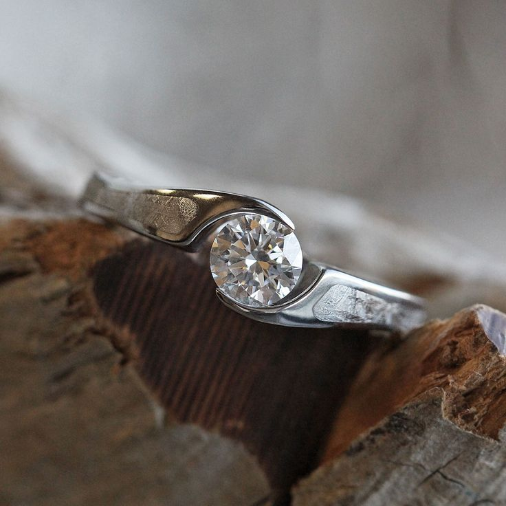 This one of a kind tension set diamond engagement ring is handmade just for her. The titanium wedding ring has meteorite inlaid on each side of the...