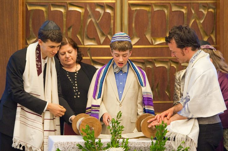 This image depicts a young man engaging in the Jewish ritual know as Bar Mitzvah. Within the jewish culture men will have a Bar Mitzvah to symbolize their transition from childhood to adult hood. The ritual functions as a event that brings family and friends together to reinforce beliefs and celebrate religious traditions.