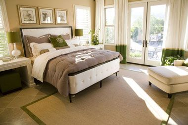 this master bedroom is romantic and elegant with soft, plush bed, chaise lounge, and soothing color scheme, although the rug could be larger