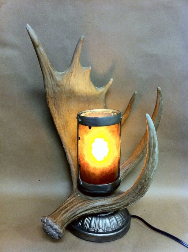 "This large moose antler lamp isn't made from an actual moose antler - but it sure looks like it is. This antler lamp makes a unique accent for the decor of a big game hunter's cabin. The """"antler"""" is"