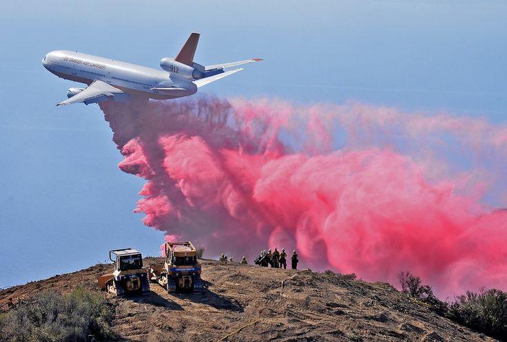 Brannmenn tar seg en pause og ser på mens et DC-10-fly tar opp kampen mot flammene i Santa Barna, California.