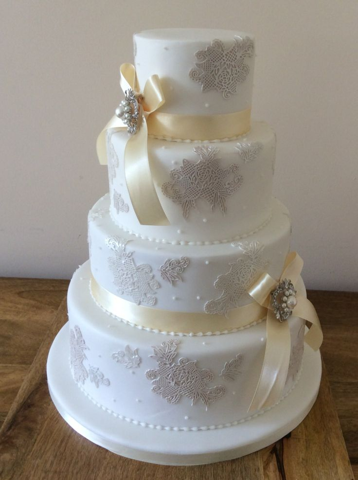 Edible lace accented four tier wedding cake | Beautiful ...