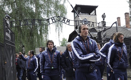 Anche se non è presente nell'immagine, vedo il fotografo e il suo compiacimento per questo scatto inequivocabile: la Nazionale Italiana è stata qui: in primo piano Chiellini, una bandiera, e sullo sfondo la scritta che sovrasta il cancello d'ingresso ad Auschwitz. Forse l'unica frase in lingua tedesca universalmente conosciuta. I ragazzi avvertono l'occhio del fotografo. Se di solito intrattengono uno sguardo complice, qui cercano e trovano l'indifferenza come forma della compostezza.