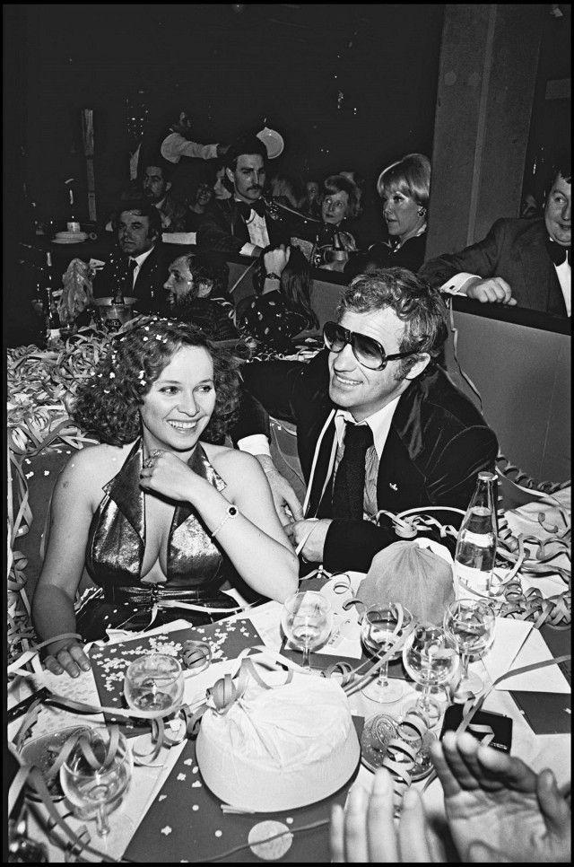 Laura Antonelli wears a metallic dress with Jean-Paul Belmondo in 1976