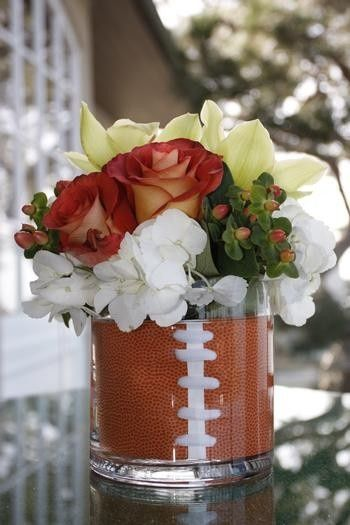 I like the football wrap inside the glass vase.  Not the flowers.  We could have the coils coming out with the basketballs and footballs.