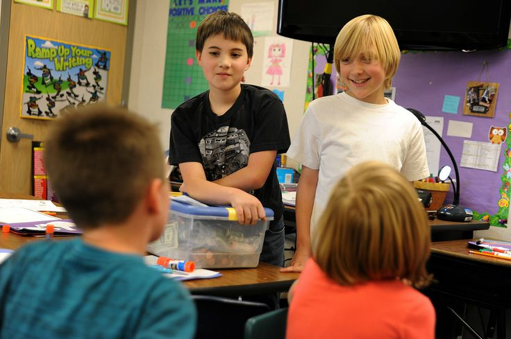 "Fifth graders Logan Nestelroad, 10, and Logan Duncan, 10, announce the results of a ""quarter war,"" a weeklong schoolwide event that raised funds for the Wounded Warrior Project, Dec. 17 at Remington Elementary School in Falcon School District 49. Duncan and Nestelroad spent time after school the past week to count each classroom's donations and make deposits. With the results tallied, they traveled to second grade teacher Trisha Butler's classroom to tell her students they raised the most…"