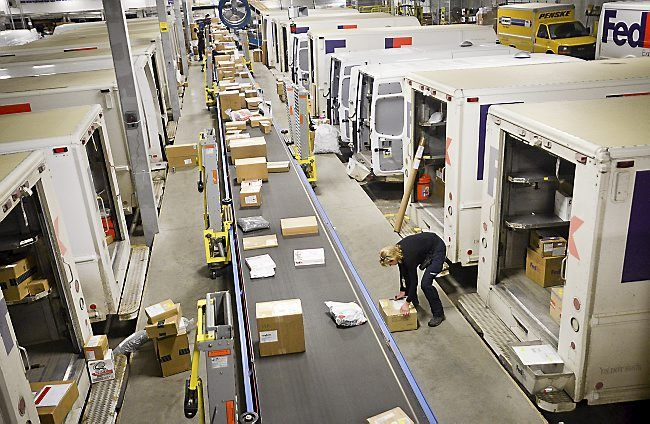 FedEx drivers grab packages off a conveyor belt as they load their delivery trucks at a FedEx shipping facility in Roseville