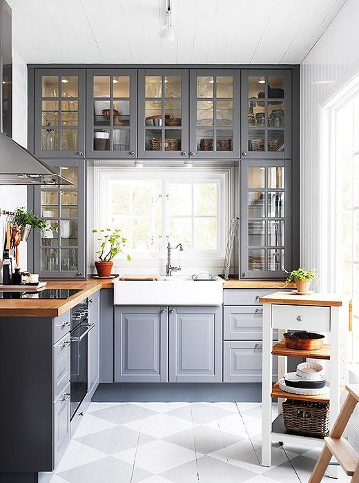 Lovely grey and white kitchen with butcher-block counters.