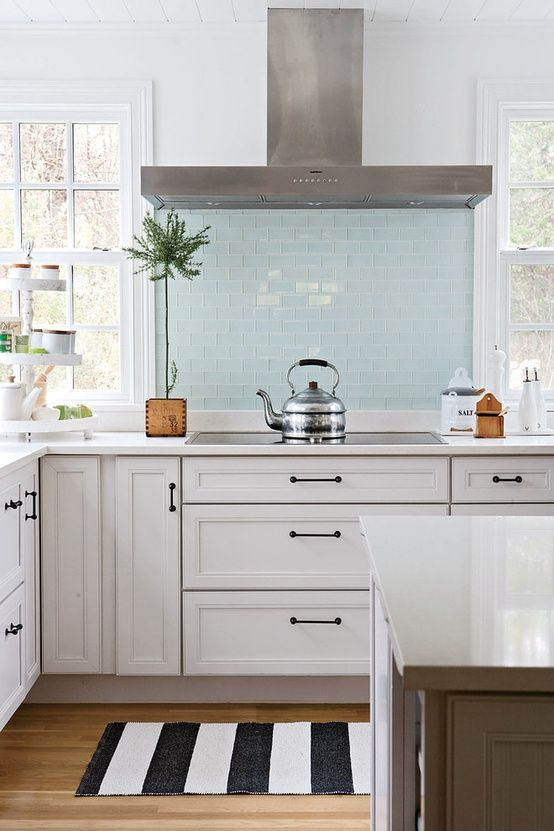 Absolutely gorgeous kitchen. Steel appliances, white cabinets, black handles, island, white walls, blue tile backsplash.. so open.