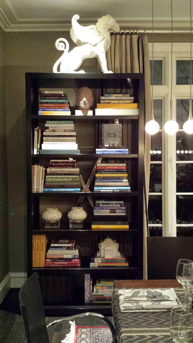 Vern Yip prefers horizontal stacks of books in lieu of vertically organizing them.    And mixing in decorative items.