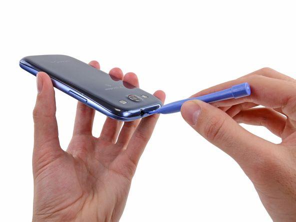 1. De følgende fire trin kan gennemføres uden et plaståbningsværktøj. Imidlertid anbefales det at bruge et værktøj for at undgå at knække nogle af de klips, der sidder langs kanten af det bagcoveret. Pres forsigtigt et plaståbningsværktøj eller en negl i hullet i området mellem bagcoveret og resten af telefonen, som ligger på toppen af enheden.