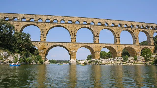 WS View of young woman and man canoeing on river Gardon with Pont du Gard bridge / Pont du Gard, Provence, France