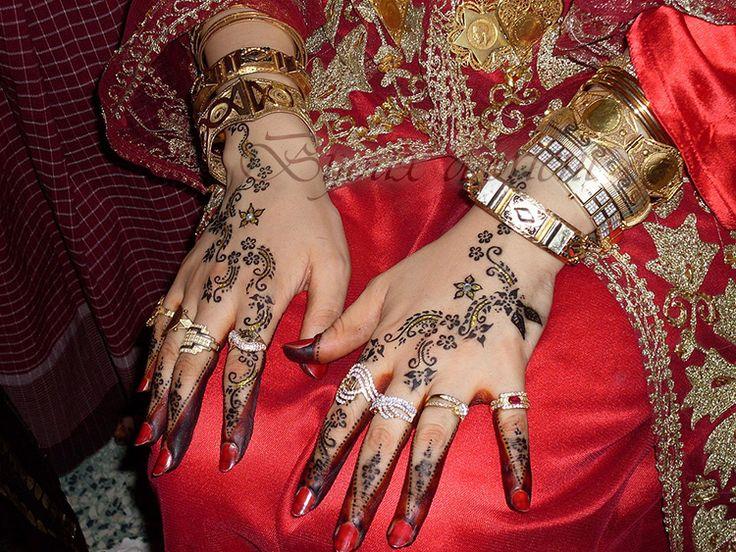 Sur sa robe rouge, une mariée tunisienne montre ses mains précieusement parées.