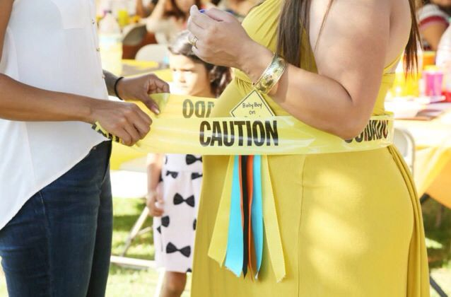 Under construction baby shower using caution tape for tummy measuring game