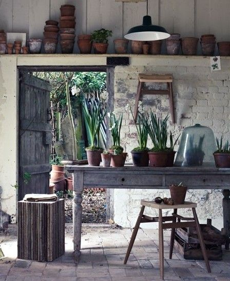 So many nice things about this work space. The old door, the square wood stool and the handy step ladder for the stored pots.