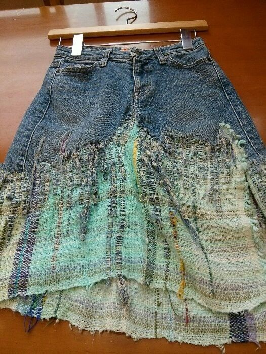 looks like she has shredded the jeans and woven pieces through the cloth added. Or maybe woven the cloth right onto the jean bits. So clever.
