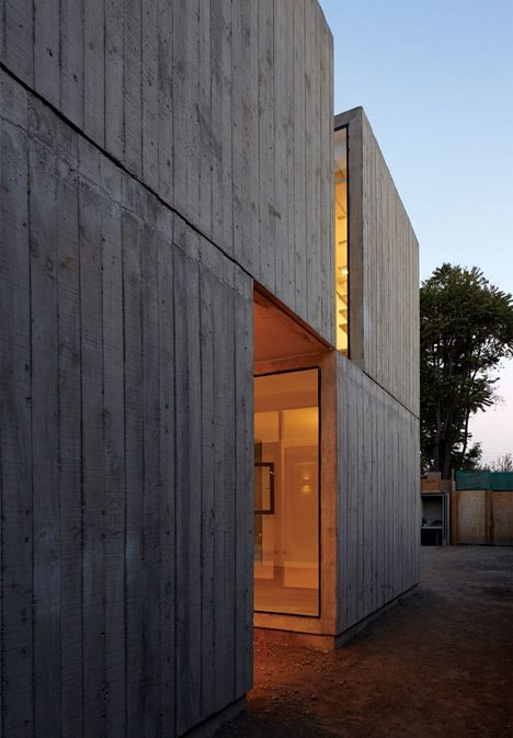 Chilean architect Ricardo Torrejón wanted to integrate the garden into this concrete house in Santiago, so he added huge windows at the back and glazed recesses along the front and sides