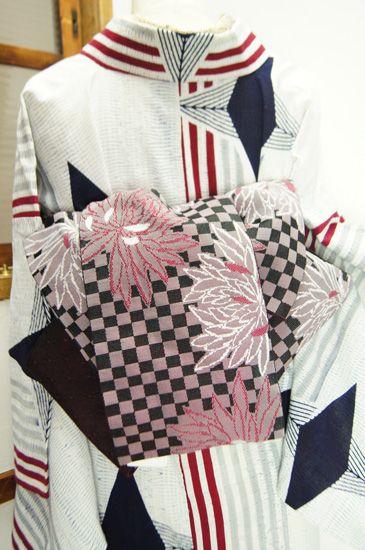 深い赤をほのかに透かす黒と白の市松文様に、大輪の菊花が重ねられた半幅帯です。
