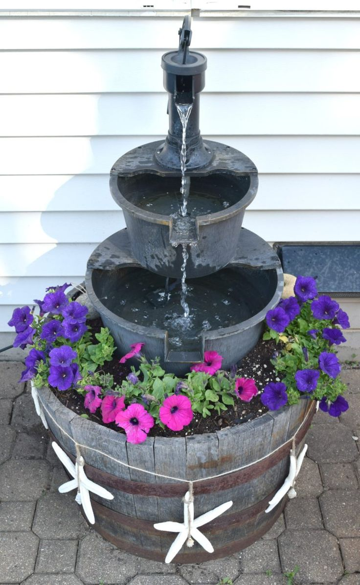 DIY water fountain, adding flowers and making the store bought water feature become a stand out for the outdoor space. Simple DIY outdoor project using a wine barrel, plywood and 2x4's is all that is needed for this water fountain update.