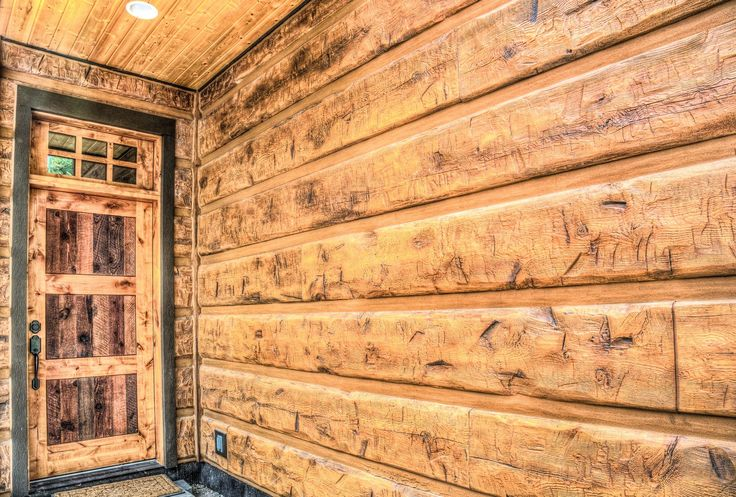 """The owners of this Flathead Lake cabin chose EverLog Concrete Log Siding in our 16"""" Hand-Hewn profile. The siding was delivered to this Kings Point getaway pre-finished in our standard Golden and screwed onto the walls with self-tapping screws. Finally it was finished off with chinking to give it the completed log home log without all the maintenance you would typically expect when using real wood log siding."""