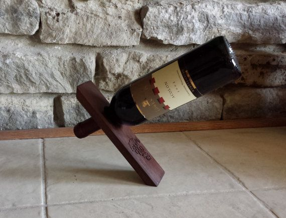 Custom Wine Bottle Holder has grapes engraved on the front. This Wine Bottle holder defies gravity!  Made from Peruvian walnut and finished with